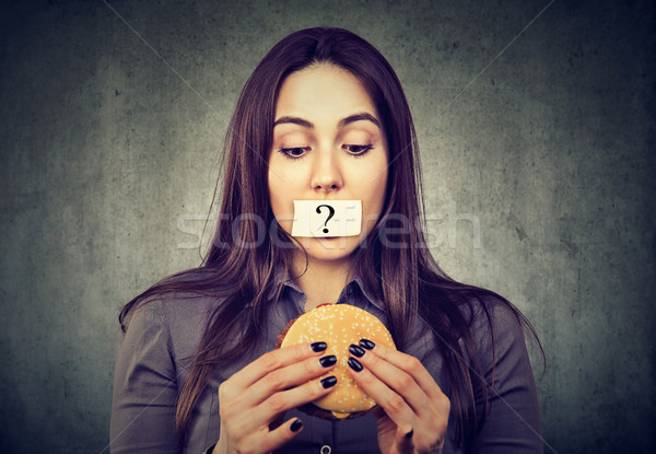 Woman on diet restriction with question mark on mouth looking at burger Stock photo © ichiosea