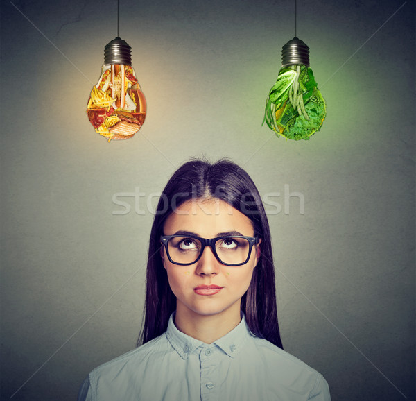 Woman in glasses thinking looking at junk food and green vegetables light bulb  Stock photo © ichiosea