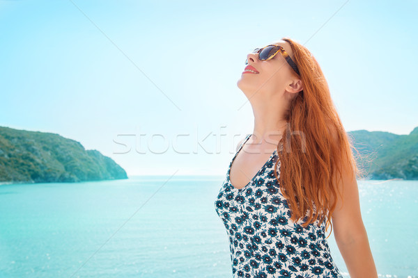 Woman smiling taking deep breath enjoying freedom and good weather by the sea. Positive human emotio Stock photo © ichiosea