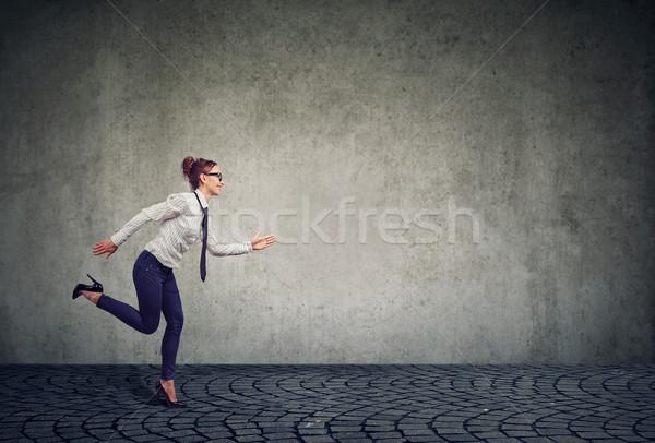 Businesswoman running against gray wall Stock photo © ichiosea
