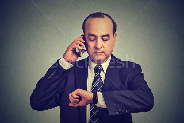 Business man looking at wrist watch, talking on mobile phone running late for meeting. Time is money Stock photo © ichiosea