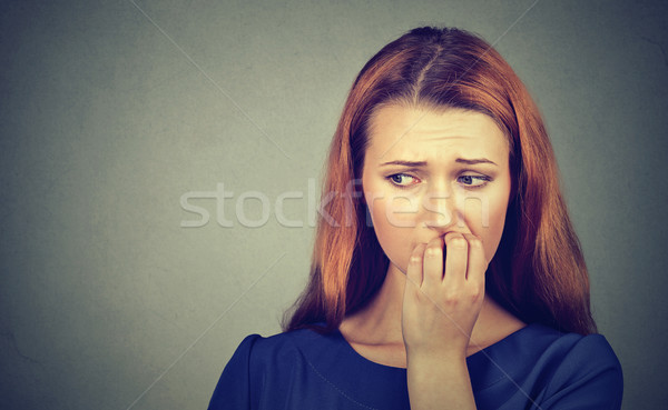 Nervous woman biting her fingernails craving something or anxious Stock photo © ichiosea