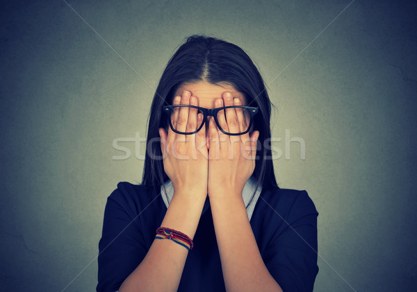 Stock photo: woman in glasses covering face eyes using her both hands