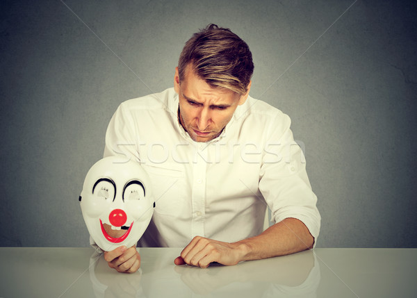 worried man with sad expression holding clown mask expressing cheerfulness Stock photo © ichiosea