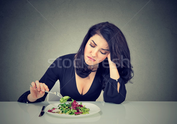 Displeased young woman eating green leaf lettuce tired of diet restrictions  Stock photo © ichiosea