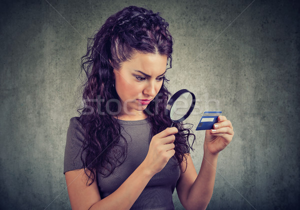 Curious woman looking at credit card through magnifying glass Stock photo © ichiosea