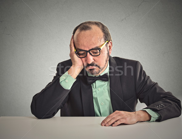 Desperate businessman sitting leaning on a desk looking down Stock photo © ichiosea