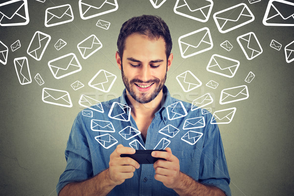 Portrait young happy man busy sending messages emails from smart phone Stock photo © ichiosea