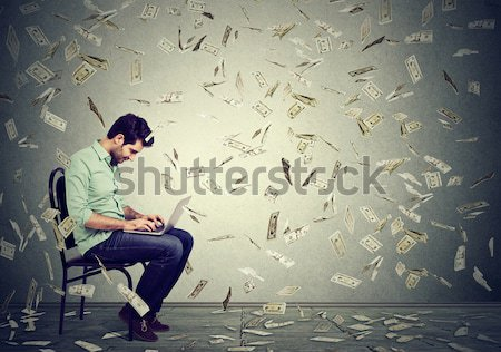 Young man using a laptop building online business making money Stock photo © ichiosea