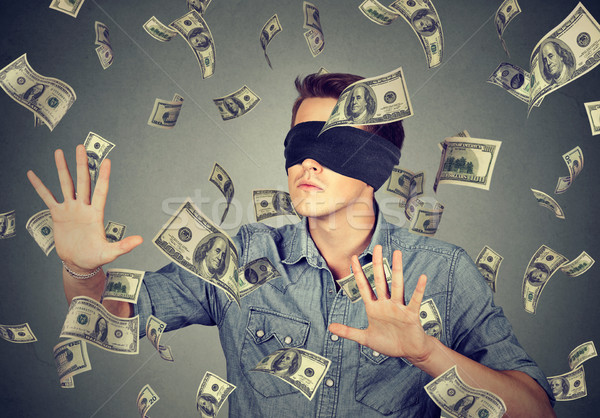 Blindfolded man trying to catch dollar bills banknotes flying in air  Stock photo © ichiosea