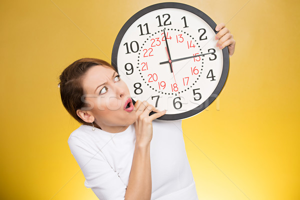 Stressed woman holding clock looking anxiously running out of time Stock photo © ichiosea
