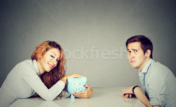 Happy wife with piggy bank sitting across the table from sad husband Stock photo © ichiosea