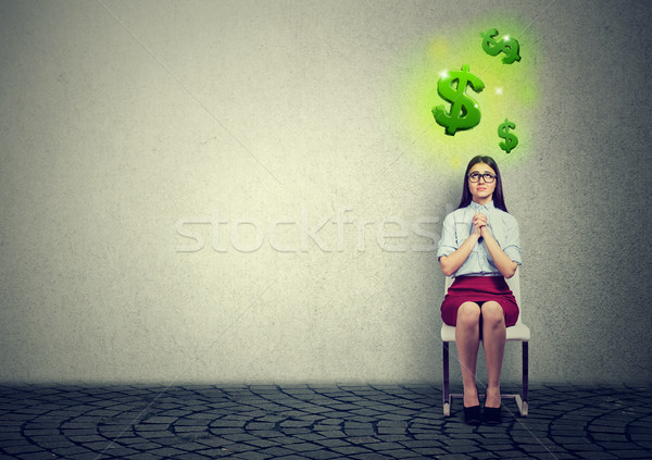 business woman sitting on chair with hands clasped praying  looking at dollar symbols above Stock photo © ichiosea