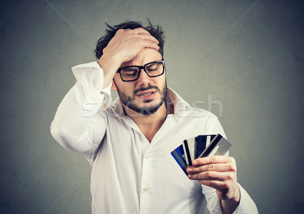 Stressed man having debts with credit card Stock photo © ichiosea
