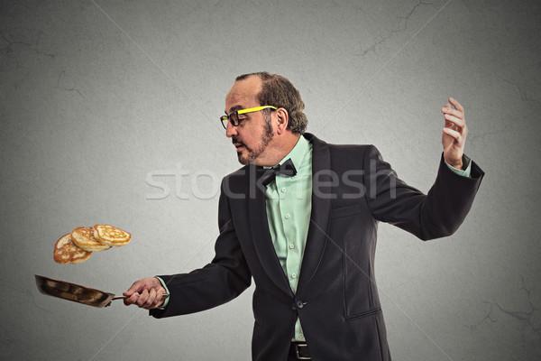 smiling man tossing pancakes on frying pan Stock photo © ichiosea