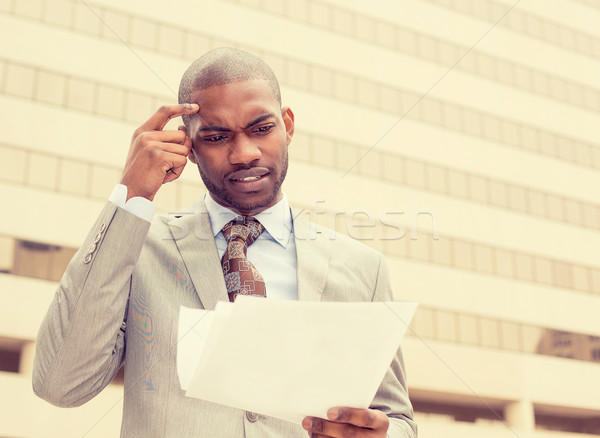 Confused executive man looking at documents outside corporate office building   Stock photo © ichiosea