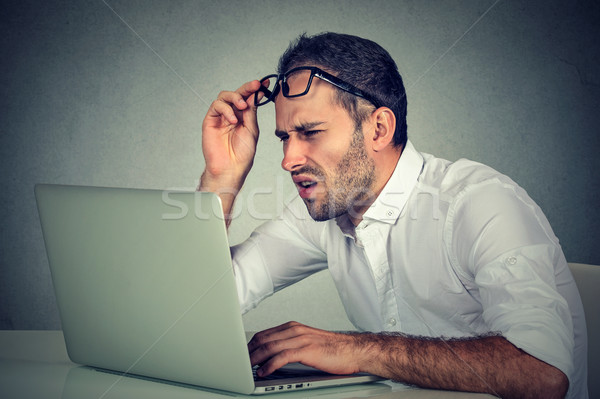 man with glasses having eyesight problems confused with laptop software  Stock photo © ichiosea