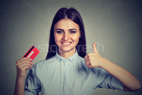 Smiling woman holding a credit card giving thumbs up  Stock photo © ichiosea