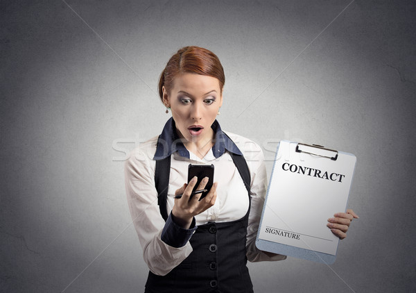 Stock photo: shocked woman holding contract document looking at smartphone