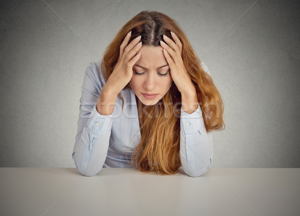 Desperate young business woman leaning on a desk Stock photo © ichiosea