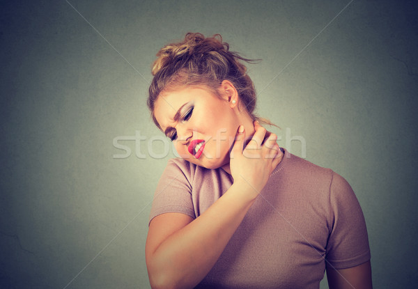 Back and spine disease. Tired woman massaging her painful neck  Stock photo © ichiosea