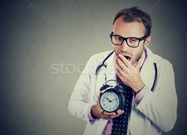 Sleepy, exhausted doctor holding alarm clock, yawning, tired after busy day Stock photo © ichiosea