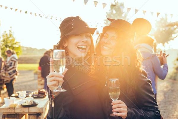 Dwa szczęśliwy młodych kobiet odkryty pitnej białe wino Zdjęcia stock © ichiosea