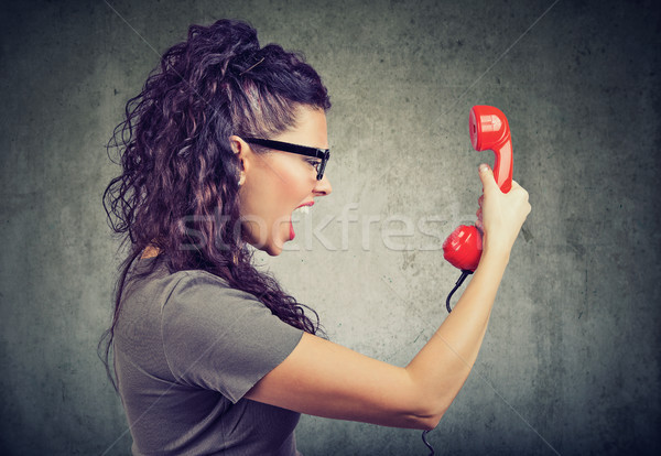 Woman holding red telephone receiver and yelling in anger.  Stock photo © ichiosea