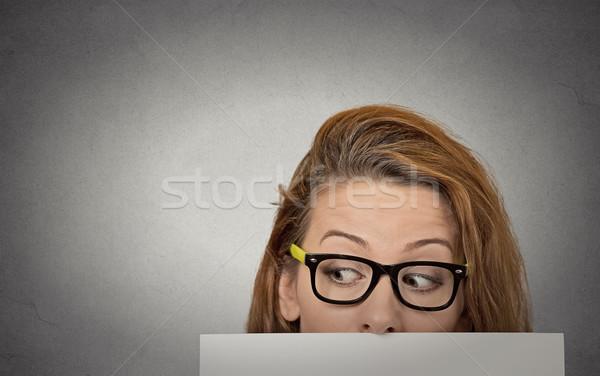Curious woman peeking over edge of blank empty paper billboard Stock photo © ichiosea