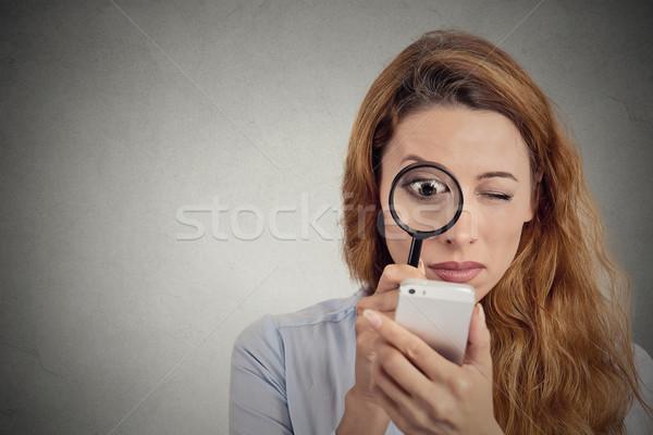 Nő néz nagyító okostelefon képernyő kíváncsi Stock fotó © ichiosea
