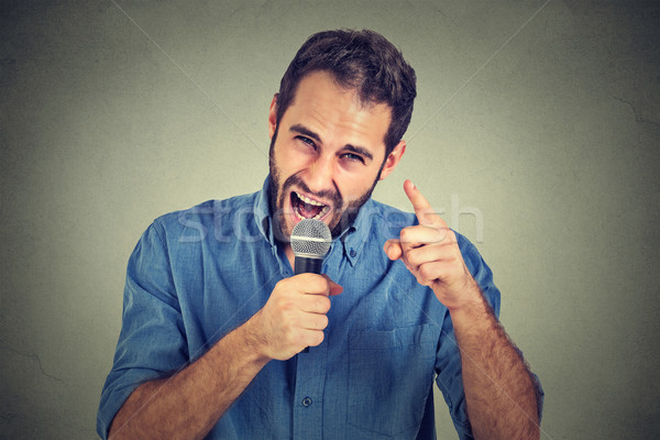 Angry man screaming in microphone Stock photo © ichiosea