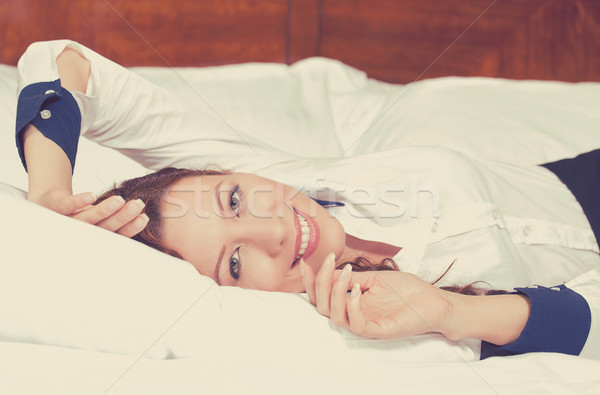 Cheerful woman lying on the bed at home daydreaming resting. Wellbeing and beauty concept  Stock photo © ichiosea