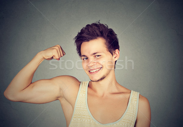 Fit and muscular young man flexing his biceps  Stock photo © ichiosea