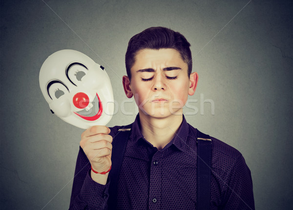 Sad man taking off happy clown mask. Split personality Stock photo © ichiosea