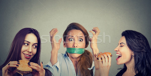 Two happy women eating hamburgers looking at stressed girl with measuring tape around her mouth.  Stock photo © ichiosea