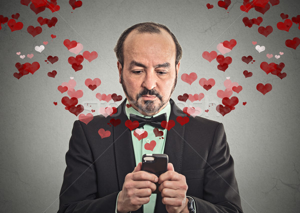 man sending love sms with mobile phone Stock photo © ichiosea