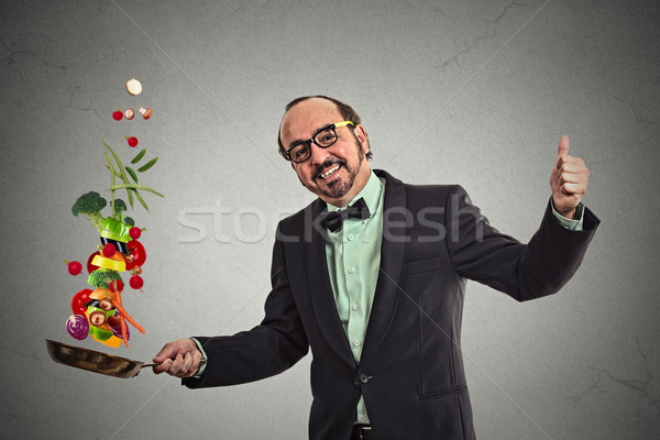 Businessman cooking vegetables with a pan  Stock photo © ichiosea
