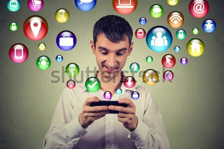 Happy man using texting on smartphone social media application icons flying out Stock photo © ichiosea