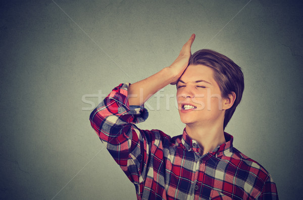 silly young man, slapping hand on head having a duh moment  Stock photo © ichiosea