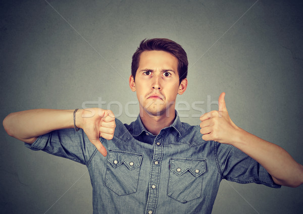 Perplexed man with thumbs down thumbs up gesture  Stock photo © ichiosea