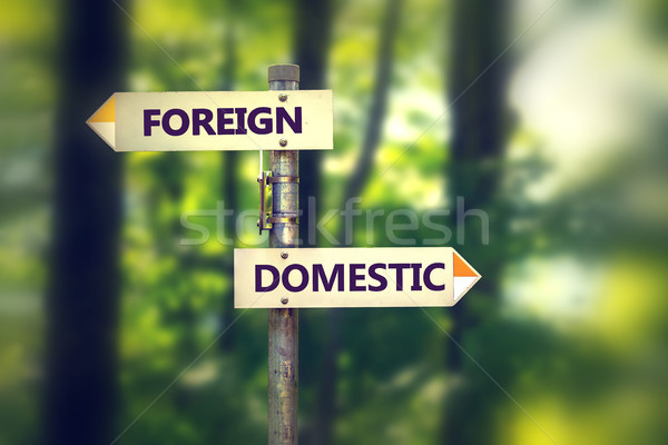 Signpost with arrows pointing in opposite directions Foreign and Domestic  Stock photo © ichiosea