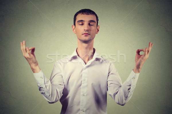Young man meditating isolated on gray wall background  Stock photo © ichiosea
