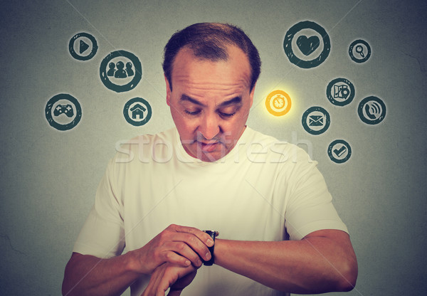 Middle age man using checking time on his smart watch with apps icons. New technology gadget concept Stock photo © ichiosea