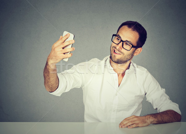young funny looking man taking pictures of him self with smart phone Stock photo © ichiosea