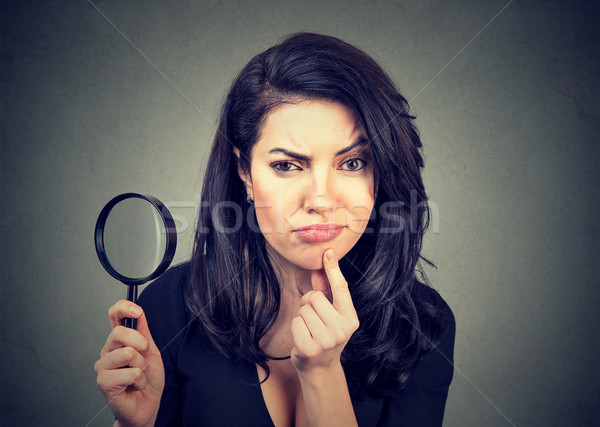 Curious young woman with magnifying glass Stock photo © ichiosea
