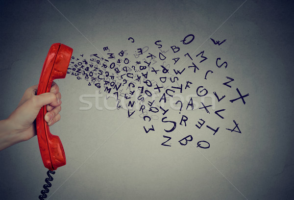 Hand holding telephone handset with alphabet letters coming out. Too many words  Stock photo © ichiosea