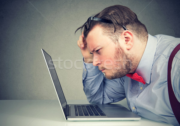 Business man taking off his glasses having eyesight problems confused with laptop  Stock photo © ichiosea