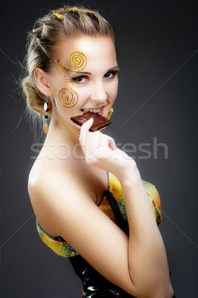 Stock photo: Happy yang woman eating chocolate bar