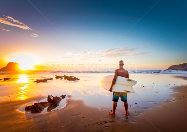 Surfer молодым человеком пляж доска для серфинга глядя волны Сток-фото © iko