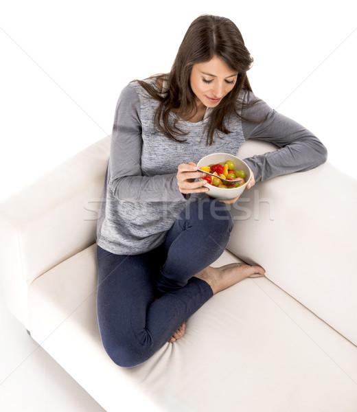 Megnyugtató gyümölcssaláta gyönyörű nő kanapé eszik étel Stock fotó © iko